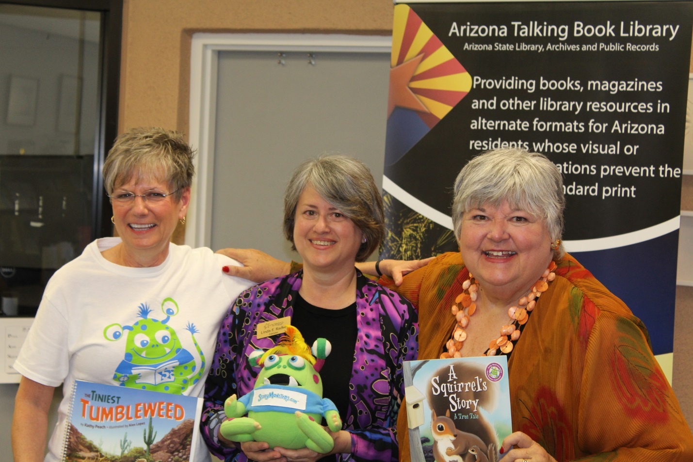 photo of Authors Kathy Peach and Jana Bommersbach with Five Star Publications owner Linda Radke holding a stuffed Story Monster toy.